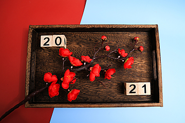 red plum blossom and 2021 number plate on dark brown wooden tray
