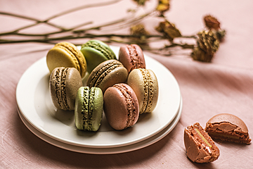 close up of macarons erected on white dish
