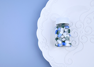 a bottle of capsules on a white dinner plate with blue background
