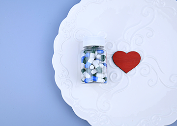 a bottle of pills and love hearts on a dinner plate with blue background