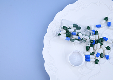 a bottle of pills on a dinner plate with blue background