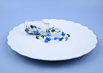 a bottle of pills on a white dinner plate with blue background