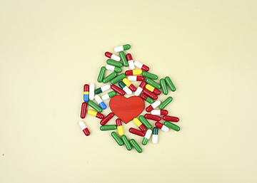 capsule pills and love heart on light yellow background