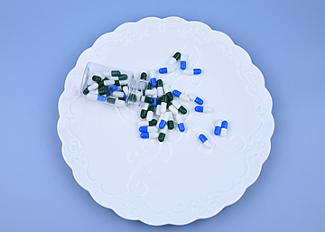 capsule pills in a bottle on blue background dinner plate