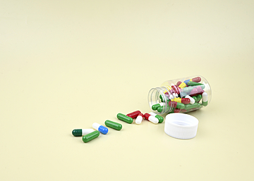 capsule pills in a bottle on light yellow background