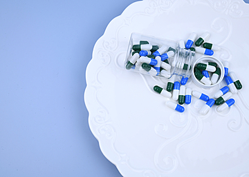 capsule pills in a bottle on white dinner plate with blue background