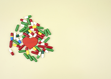 capsules and love hearts on light yellow background