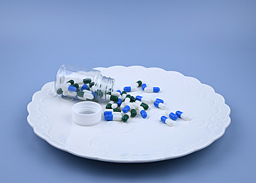 capsules in a bottle on blue background dinner plate