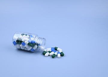 capsules in a bottle on blue background