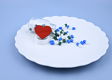 dinner plate with love hearts and a bottle of capsules on blue background