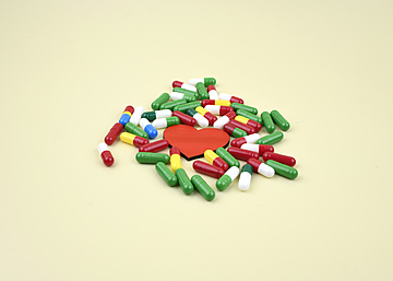 pills and love heart on light yellow background