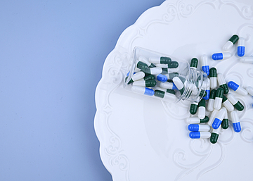 pills capsules on blue background dinner plate