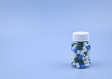 pills in a bottle on blue background