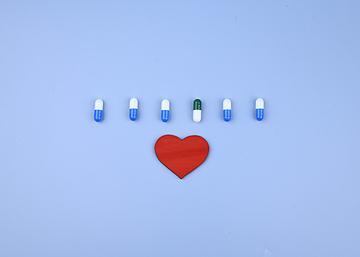 six capsules and love hearts on blue background