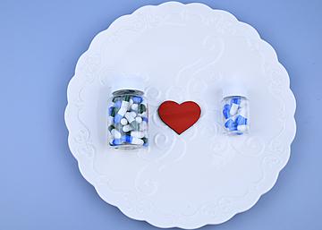 two bottles of capsule love on blue background dinner plate