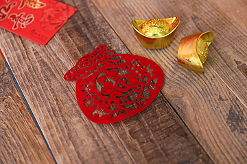 gold ingots and paper cut fu on wooden table