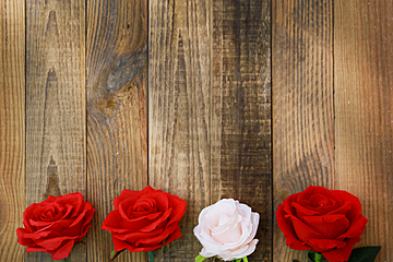 valentines day background with four roses placed on wooden board