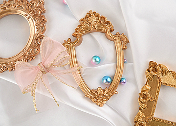three photo frames with pearl bows on white