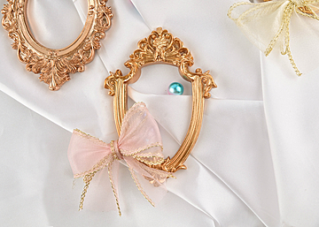 two photo frames with bows and pearls on white background