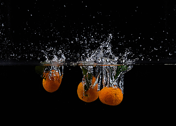 water splash and three oranges falling into water
